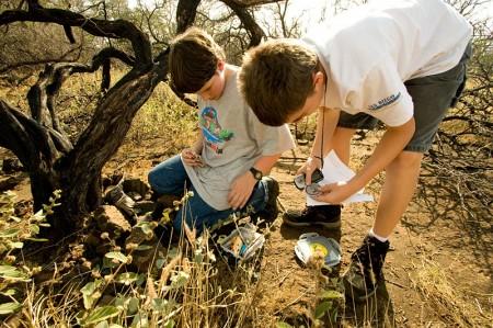 The boys explore the geocache in Puako.
