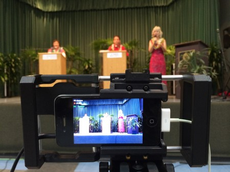 An iPhone 4 in a BeastGrip tripod mount, audio from the board coming in on the left, external power supply coming in on the right, video streaming live on Ustream. This was at the Senate candidates debate in Hilo, Hawaii. Photo by Baron Sekiya