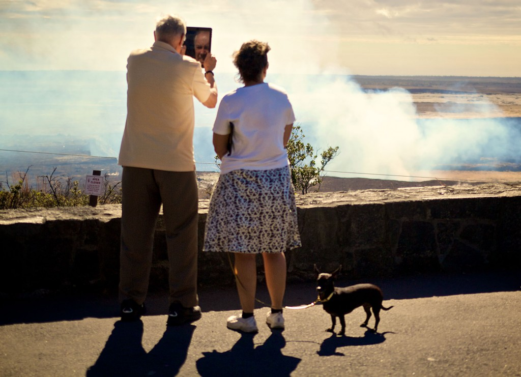 Got a quick snapshot of this couple and their dog visiting Halemaumau, didn't even notice at the time that the guy's face was reflected in his tablet while he shot a photo. The dog appears to be uninterested but then again at his level he can't see anything on the volcano side. Photo by Baron Sekiya